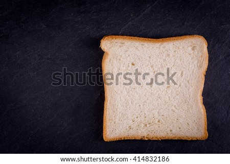 closeup of a slice toast bread on dark slate background with copy-space - stock photo