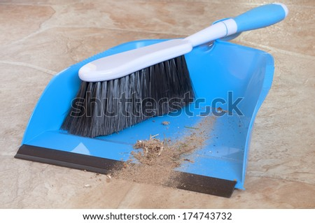 Closeup of a Small Whisk Broom with Short Handle and a Dustpan with Real Dirt Swept off Floor - stock photo