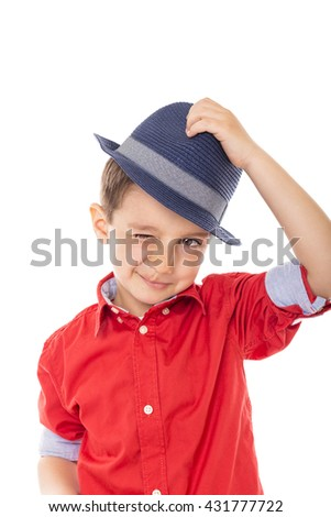 Closeup of a smiling little boy blinking holding a hat over white background