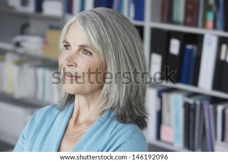 Closeup of a smiling middle aged businesswoman looking away in office - stock photo