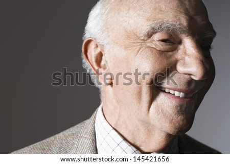 Closeup of a smiling senior man against gray background