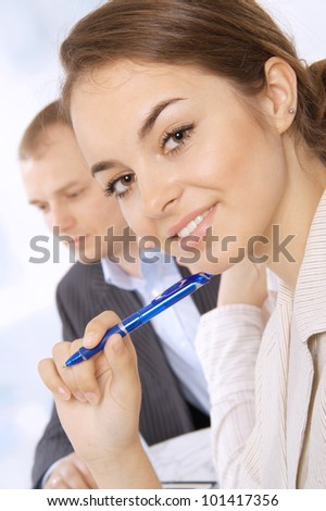 Closeup of a smiling young business executive in a meeting with colleagues - stock photo
