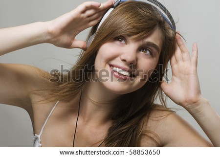 Closeup of a smiling young woman listening music