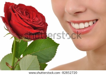 Closeup of a smiling young woman with red rose - stock photo