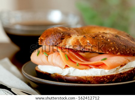 Closeup of a smoked salmon and cream cheese bagel with coffee. - stock photo