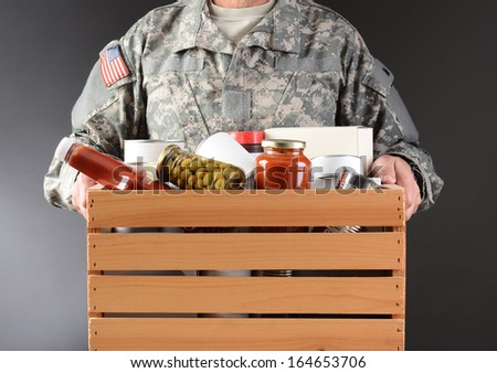 Closeup of a soldier in fatigues holding a wooden box full of canned and packaged food for a holiday charity drive. Horizontal format man is unrecognizable. - stock photo
