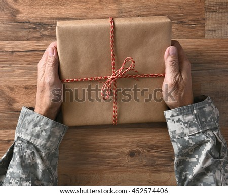 Closeup of a soldiers hands holding a plain wrapped parcel, over a wood background. - stock photo