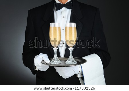 Closeup of a Sommelier holding two champagne glasses on a tray in front of his torso. Horizontal format on a light to dark gray background. - stock photo