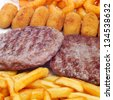 closeup of a spanish combo platter with burgers, croquettes, calamares and french fries - stock photo