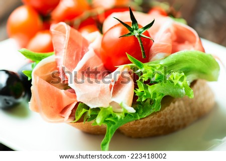 closeup of a spanish serrano ham tapas with cherry tomato - stock photo