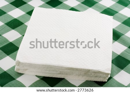 Closeup of a stack of paper napkins on top of a tablecloth - stock photo