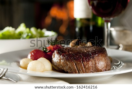 Closeup of a steak with vegetables in a restaurant setting. - stock photo