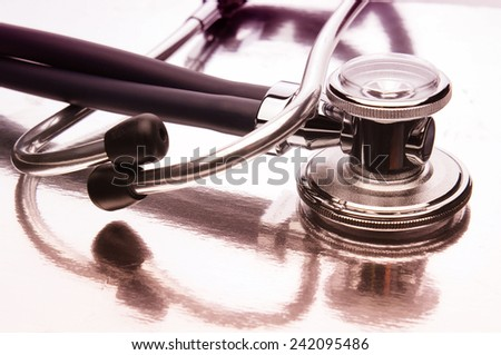 Closeup of a Stethoscope on a reflective surface with multi-color reflections. Horizontal format with shallow depth of field. - stock photo