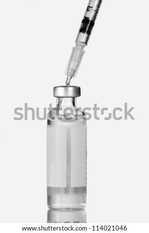 Closeup of a syringe injected into an insulin vial, bottle.  Isolated on white. - stock photo