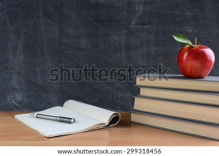 Closeup of a teachers desk with books, paper and pen and a red apple in front of a chalkboard. Horizontal format with copy space.  - stock photo