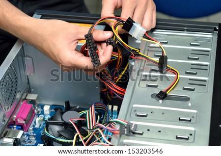 Closeup of a technician's hands wiring a computer mainboard - stock photo