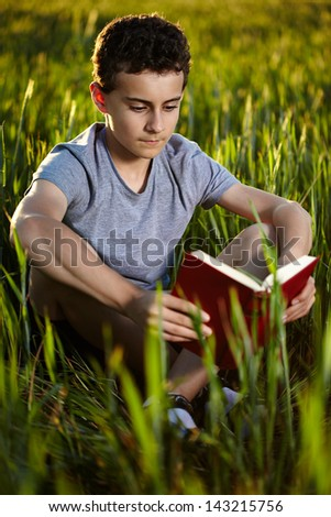 Closeup of a teenage boy reading a book in a wheat field at sunset, with selective focus - stock photo