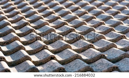 Closeup of a tiled roof in early morning light. - stock photo