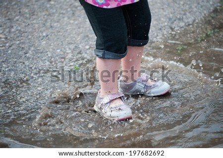 Closeup of a toddler's dirty legs and shoes as she splashes in a rain puddle - stock photo