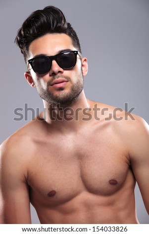 closeup of a topless young man looking into the camera with a serious expression on his face. on gray background - stock photo