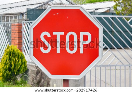 Closeup of a traffic stop sign by the road near an intersection - stock photo