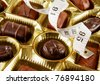 closeup of a tray of chocolates with a tape measure, concept of high calorie treats - stock photo