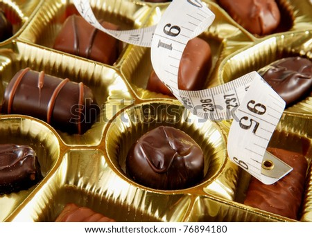 closeup of a tray of chocolates with a tape measure, concept of high calorie treats