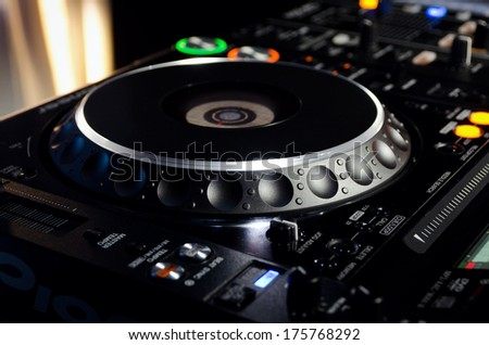 Closeup of a turntable on a Disc Jockeys music deck at a discotheque or party used to mix and scratch recorded soundtracks on vinyl records