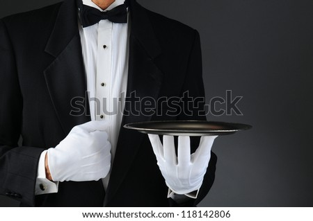 Closeup of a tuxedo wearing waiter holding a silver tray in front of his body. Horizontal format on a light to dark gray background. Man is unrecognizable.