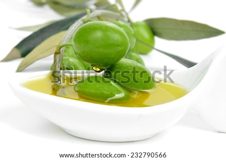 closeup of a twig of olive tree with olives on a bowl with olive oil - stock photo