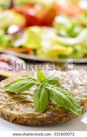 closeup of a veggie burger in a plate and a plate with salad in the background - stock photo