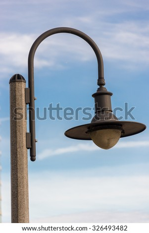Closeup of a vintage streetlamp fixed on a lamp post against the sky in the background. The lamp is facing downward while its holding rod is in 'inverted U' shape. - stock photo