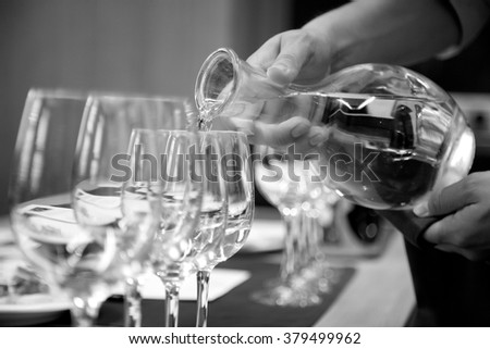 Closeup of a waiter pouring water into glasses - stock photo