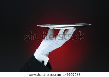 Closeup of a waiter's hand holding a silver serving tray in his fingertips over a light ot dark red background. Only the man's hand and arm are visible. He is wearing a tuxedo and formal white gloves. - stock photo