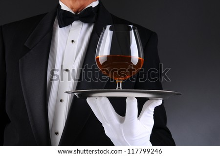 Closeup of a waiter wearing a tuxedo and holding a tray with a brandy snifter. Low angle man is unrecognizable. Horizontal format with a light to dark gray background. - stock photo