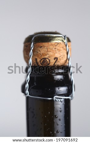 Closeup of a wet champagne bottle neck with cork