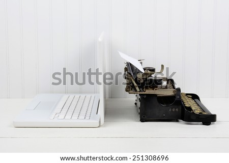 Closeup of a white desk with a modern laptop computer and an antique typewriter back to back. Horizontal format with copy space. Old vs new concept. - stock photo