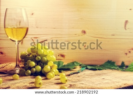 Closeup of a white wine glass surrounded by wooden texture.