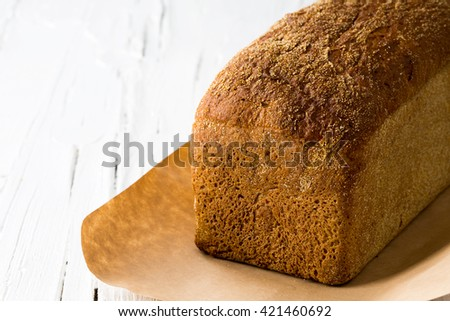 Closeup of a whole loaf of bread on white wooden background. - stock photo