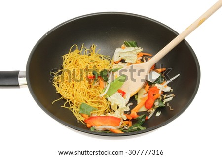 Closeup of a wok with stir fry vegetables and noodles with a wooden spoon isolated against white - stock photo