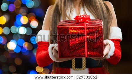 Closeup of a woman dressed in Christmas cloths holding a present - stock photo