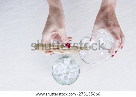 closeup of a woman hand filling a balloon glass with ice from an ice bucket with a bamboo ice tongs on a gin tonic preparation session - focus on the ice cube - stock photo