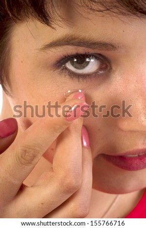 Closeup of a woman inserting a contact lens in her eye - stock photo