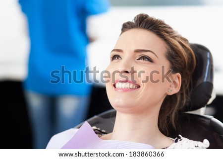 Closeup of a woman patient at the dentist waiting to be checked up with the woman doctor in the background - stock photo