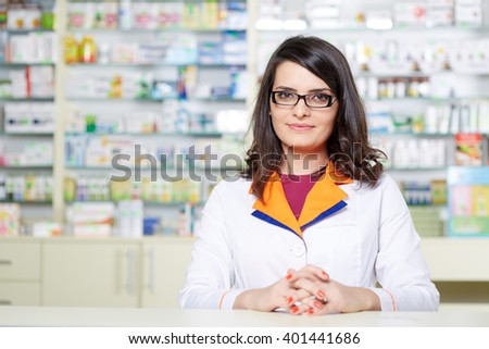 Closeup of a woman pharmacist over blurred background of shelves with medicine