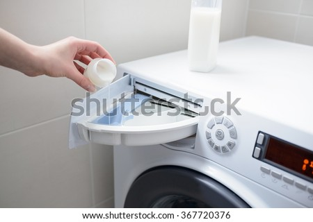 Closeup of a woman's hand pouring white liquid fabric softener to the washing machine