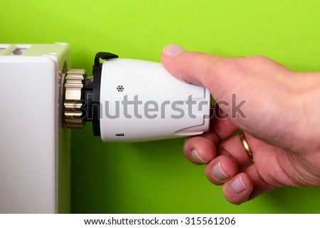 Closeup of a woman's hand setting the room temperature By Thermostat - GREEN POWER energy SAVING concept - stock photo