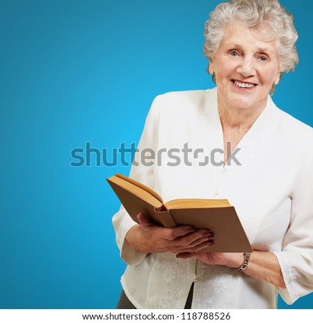 Closeup Of A Woman While Holding Book On Blue Background - stock photo