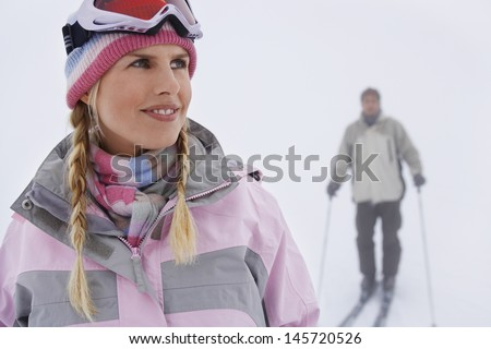 Closeup of a woman with man skiing in background on slope - stock photo