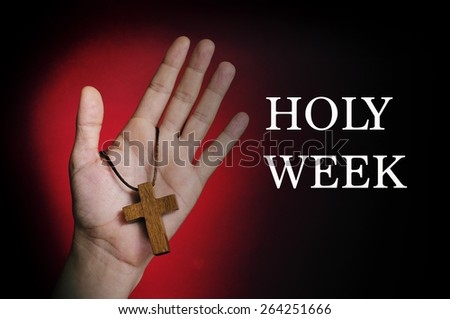 closeup of a wooden cross in the hand of a young caucasian man and the text holy week written in white on a red and black background - stock photo